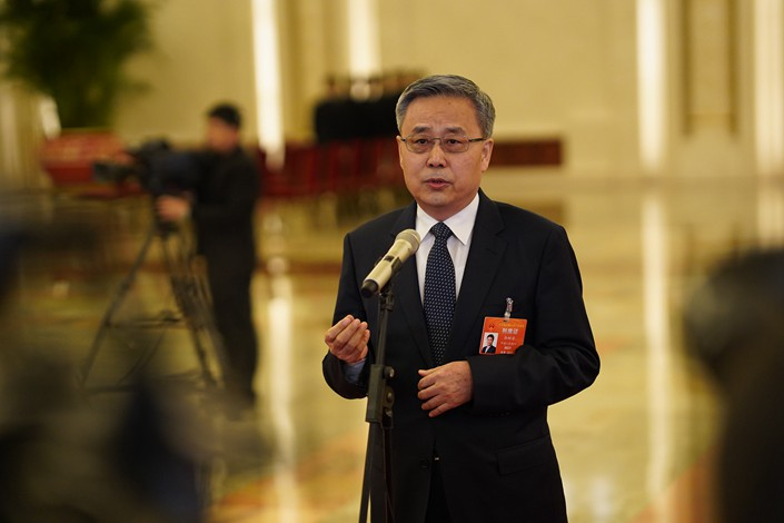 Guo Shuqing, chairman of the China Banking and Insurance Regulatory Commission, answers reporters' questions Tuesday in Beijing. Photo: VCG