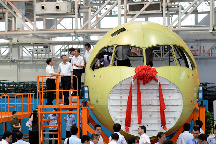 Officials inspect China's first domestically-made passenger jet, the C919, at a plant in Chengdu on July 31, 2014. Photo: VCG