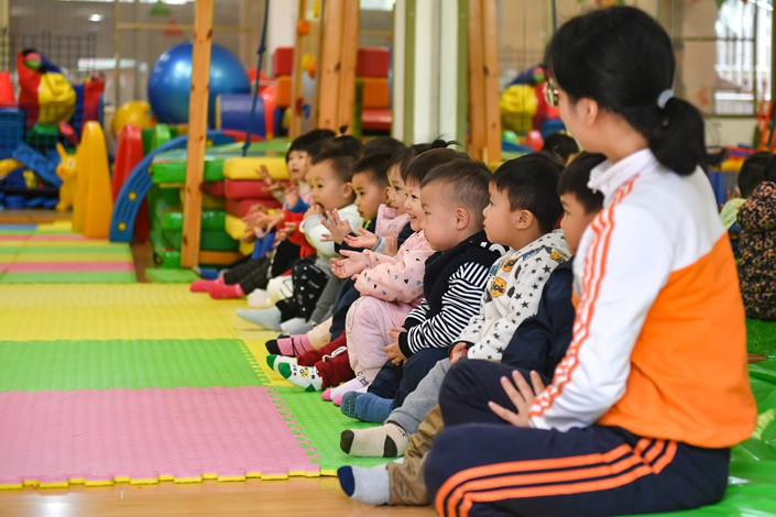 Teachers interact with children at a day care center in Guangzhou, Guangdong province on March 1. Photo: IC
