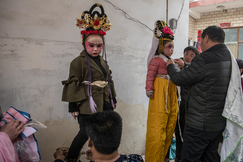 Parents help the their children prepare for the parade in Huaxian on March 4. Photo: VCG