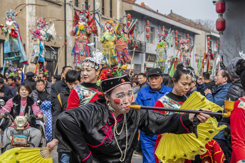 A local performer pretends to smoke a pipe during the parade in Huaxian on March 4. Photo: VCG