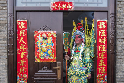 A performer in the costume of door god stands at the gate of a house in Huaxian on March 4. Photo: VCG