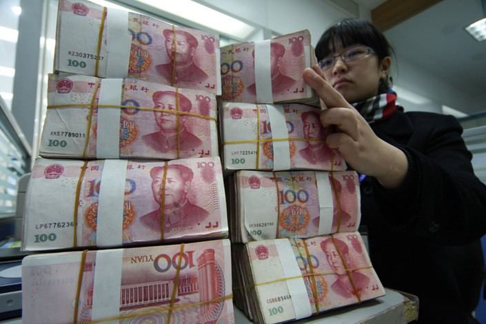 A bank clerk counts cash at a bank in Nantong, East China's Jiangsu province. Photo: IC