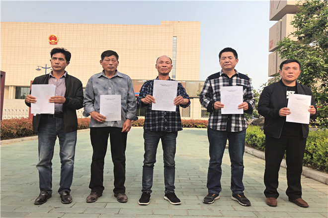 The 'Five Zhous' show reporters court documents declaring them not guilty of homicide, outside the Anhui High People's Court on April 11, 2018. Photo: Xiao Hui/Caixin