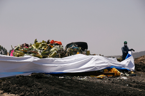 A local worker covers the debris of Ethiopian Airlines Flight ET 302 before the commemoration ceremony begins on Wednesday. Photo: VCG