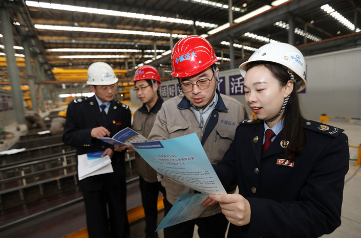 Tax department employees publicize policy changes at a company in Anhui province on March 6. Photo: VCG