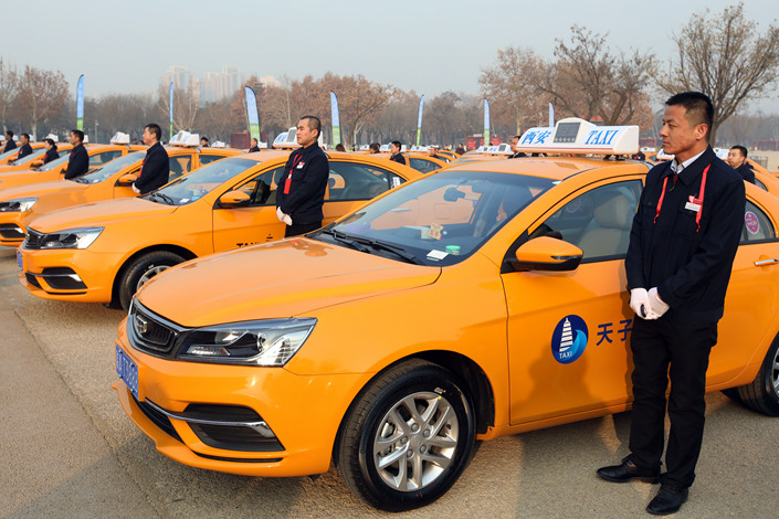 Drivers stand beside taxis that run on pure methanol in Xi'an, Shaanxi, on Dec. 20, 2018. Photo: IC