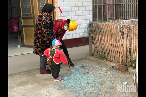 A villager in a helmet cleans up broken glass on the ground Friday in Xiangshui. Photo: Caixin
