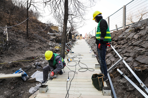Two laborers work on the boardwalk, March 26. Photo: IC