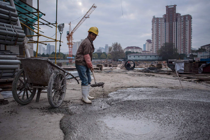 A worker fills a wheelbarrow with cement at a construction site in Shanghai in Nov. 29. Photo: VCG