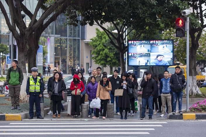 People wait at a pedestrian crossing in Guangzhou, Guangdong province on Feb. 25. To discourage traffic violations, people who cross when the light is red will be filmed by a video camera and the footage will be replayed on a big screen. Photo: VCG