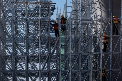 Workers with hard hats stand on scaffolding at the site of the future Xiongan Railway Station on March 23. Photo: IC