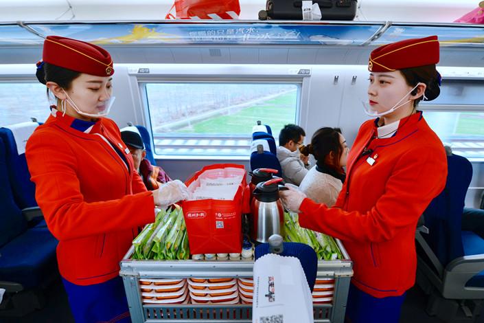 Attendants serve passengers on a high-speed train on Jan. 26. Photo: IC