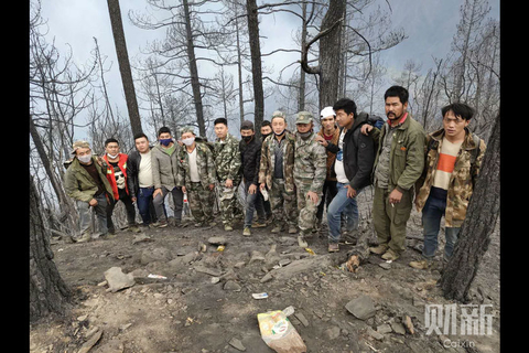 Villagers prepare to take the remains of the first victims of the fire down a hill on Tuesday. Photo: Cao Jianhua