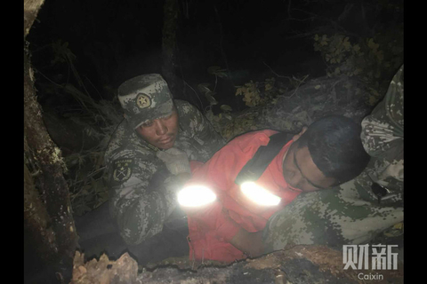 Firefighters who survived an encounter with the fire rest in a cave on Monday. Photo: Ying Wujin