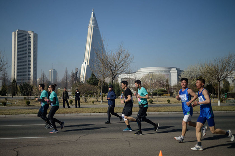 Competitors run past the unopened Ryugyong Hotel (center) during the marathon on April 7. Photo: VCG