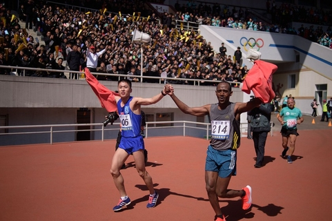 The winner of the men's full marathon Ri Kang Bom of North Korea (left) runs with a competitor from Ethiopia after crossing the finish line of the annual marathon at Kim Il Sung Stadium in Pyongyang, on April 7. Photo: VCG