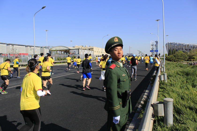 An armed police officer stands guard along the street during the Beijing Half Marathon on Sunday. The iconic Beijing National Stadium, usually referred to as the Bird's Nest, can be seen in the background. The marathon ends at the Olympic Green, also known as the Beijing Olympic Park. Photo: IC_Gallery: Running From Tiananmen to the Bird's Nest