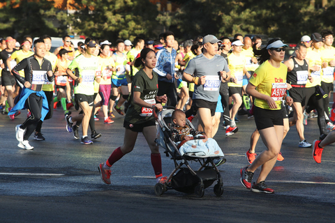 A participant runs with her child in a stroller during the Beijing Half Marathon on Sunday. Photo: IC