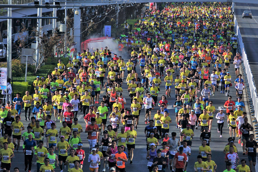 Marathon participants run past the starting line on April 14. Photo: IC_Gallery: Running From Tiananmen to the Bird's Nest
