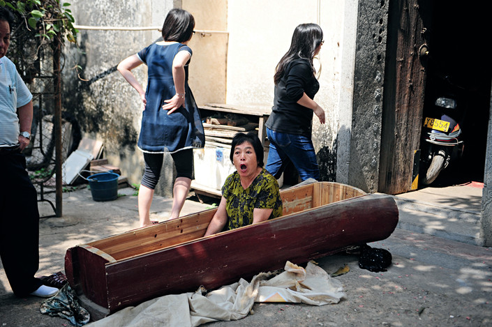 "On April 26, 2011, a man named Deng found an empty coffin on his front doorstep in Shenzhen's Longgang district. He suspected that property developers had placed it there as a threat because his family was a ""nail household"" — the term given to occupants who refuse to vacate their homes even after all surrounding homes have been sold for redevelopment. Deng reported the threat to the police, and his wife later jumped into the coffin to protect the evidence when people tried to remove it. Photo: Xu Wenge"