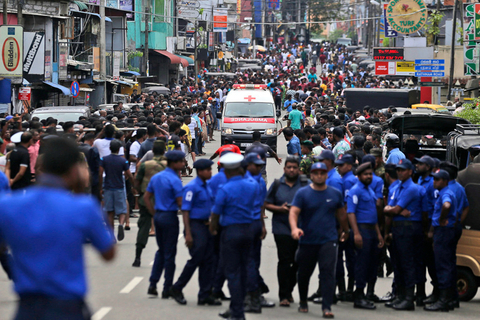 Sri Lankan police officers clear the road for an ambulance carrying people injured Sunday in the church bombings in Colombo. Photo: IC
