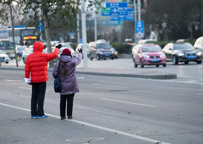 Two people attempt to hail taxis in Beijing in November, 2015. Photo: IC Photo