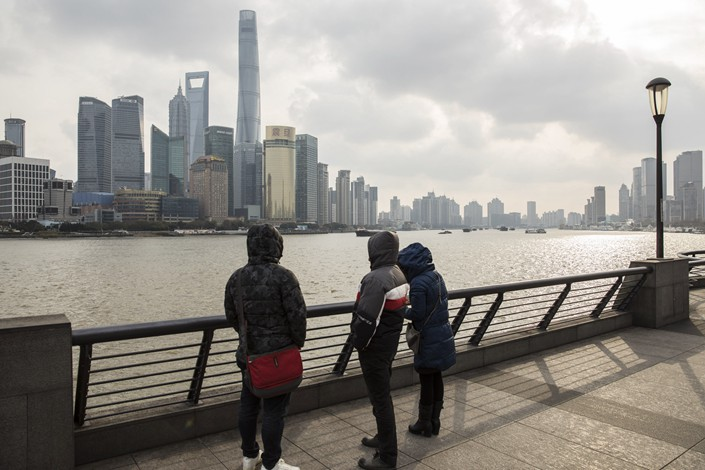 Pedestrians stand along the Bund in Shanghai. Photo: Bloomberg