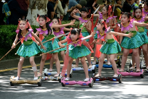 "A group of children dressed as Nezha, a Chinese mythological figure, stand on electric scooters which resemble the ""Wind Fire Wheels"" used by the deity. Photo: IC Photo"