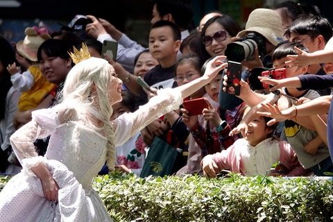 A performer dressed as Snow White interacts with spectators. Photo: IC Photo