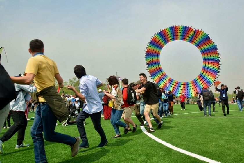 A group of people fly an enormous rainbow ring kite on May 4 during the Beijing International Kite Festival 2019 in Beijing. Photo: IC Photo_ Gallery: Dragons, Butterflies and a Kite So Big You Can Walk Through It