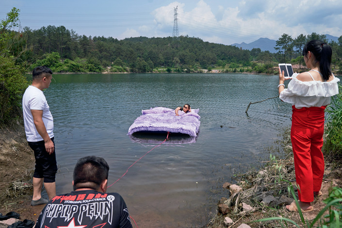 "Employees of a bedding shop film an air mattress floating on a reservoir near Yiwu, Zhejiang province. As ""live e-commerce"" took off, it became harder to attract viewers, and vendors have had to resort to all sorts of gimmicks. Photo: Liang Yingfei/Caixin"