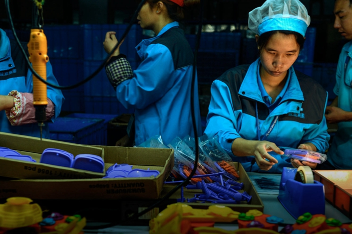 Migrant workers on a toy factory assembly line in Dongguan, Guangdong province, April 13, 2015. Photo: IC Photo