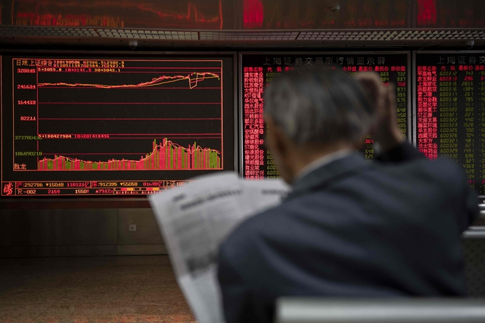 A man reads a newspaper on May 6 at a securities company in Beijing where investors can watch stock price movements. Photo: VCG