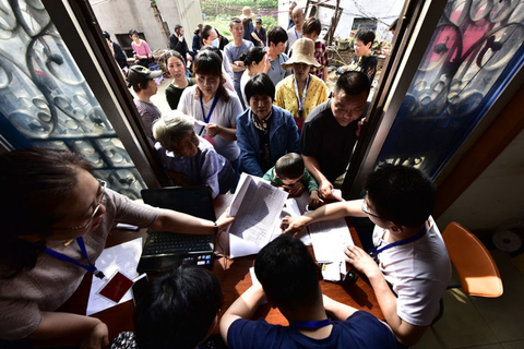 Residents whose homes are about to be demolished hand over documents related to their property to local government staff on May 14. Photo: IC Photo