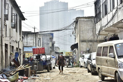 "A villager wearing a mask walks through the ""urban village"" on May 14 before demolition begins. Photo: IC Photo"