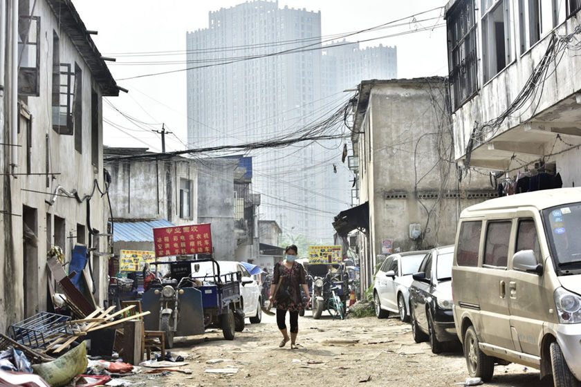 "A villager wearing a mask walks through the ""urban village"" on May 14 before demolition begins. Photo: IC Photo_Gallery: Over 14,000 Evicted for New Train Station"