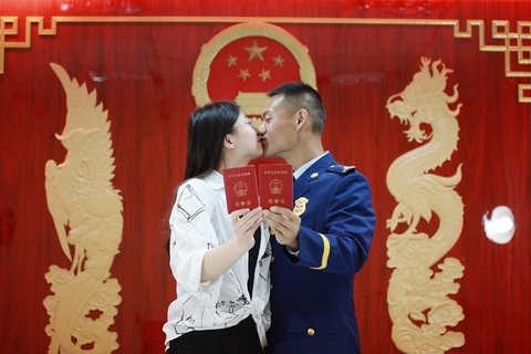 A newlywed couple shows off their marriage registration certificates Monday at a civil affairs bureau in Yangzhou, Jiangsu province. Photo: VCG