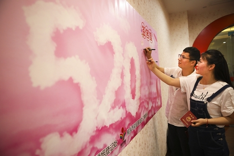 A newlywed couple signs a signature wall at the civil affairs bureau in Tongxiang, Zhejiang province. The local civil affairs department also joined hands in the figurative sense with volunteer organizations to hold a special certificate ceremony for couples on Monday. Photo: VCG