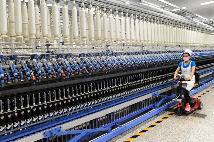 A worker inspects an automated yarn spinning workshop of Weiqiao Textile in April 2018. Photo: IC Photo