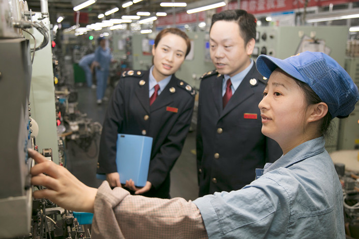 State Administration of Taxation officials speak with a worker on April 10 at a production workshop of Liuhe Electronics Co. Ltd. in Yichun, East China's Jiangxi province. Photo: IC Photo