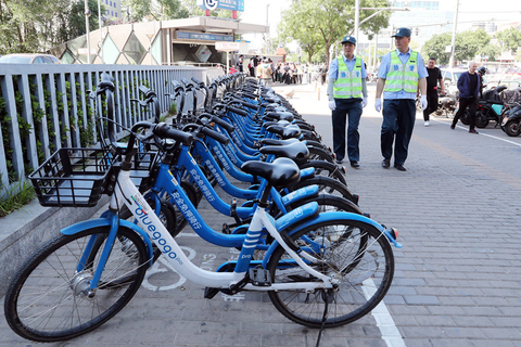 Staff check shared bikes parked on the street. Photo: VCG