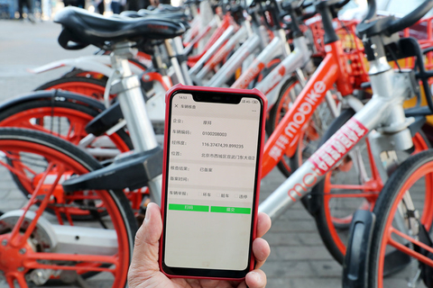 A worker uses a phone to check the information of registered shared bikes. Photo: VCG