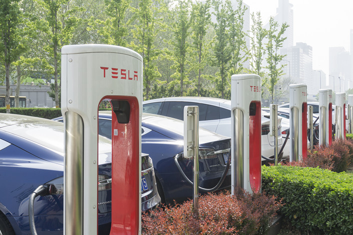 Electric-vehicle charging stations line the entrance to a Tesla dealership in Beijing on April 17. Photo: VCG