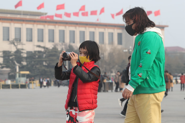 Visitors to Tiananmen Square in Beijing wear masks to protect themselves from air pollution on March 2. Photo: IC Photo