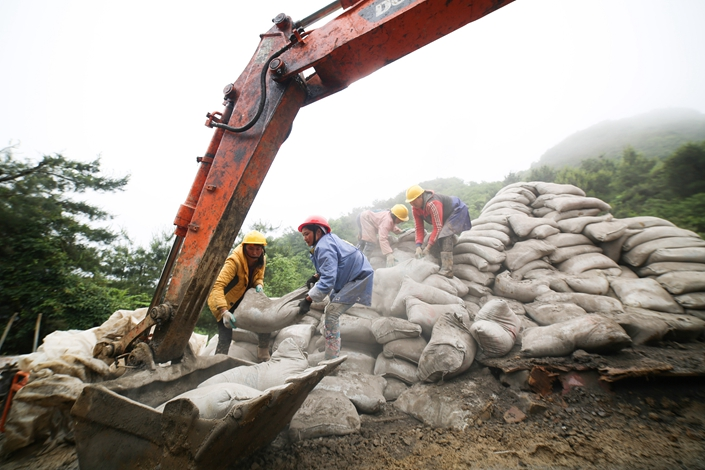 Villagers move sacks of cement on Wednesday in Southwest China's Guizhou province. Photo: VCG