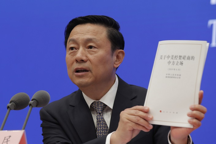 Guo Weimin, Vice Minister of the State Council Information Office, holds the White Paper on China's Position on the China-US Economic and Trade Consultations at a press conference on Sunday. Photo: IC Photo