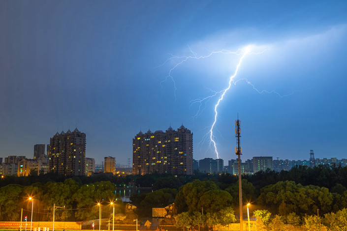Lightning crashes near a cell phone tower in Beijing on Sunday. Photo: VCG