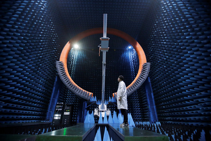 An engineer stands beside a Huawei 5G base station antenna in Dongguan, Guangdong province, on May 30, 2019. Photo: VCG
