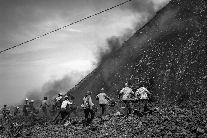 February 2007, Pingdingshan, Henan province: Without waiting for the pile to settle, collectors rush towards the gangue hill, ignoring the risks of falling debris.